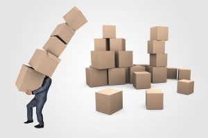 A man carrying some boxes. - Office movers Manhattan can help you with this task.