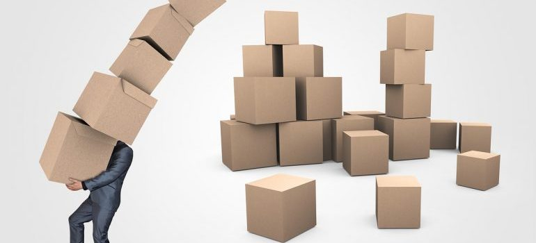 A man carrying some boxes - Office movers Manhattan can help you with this task.