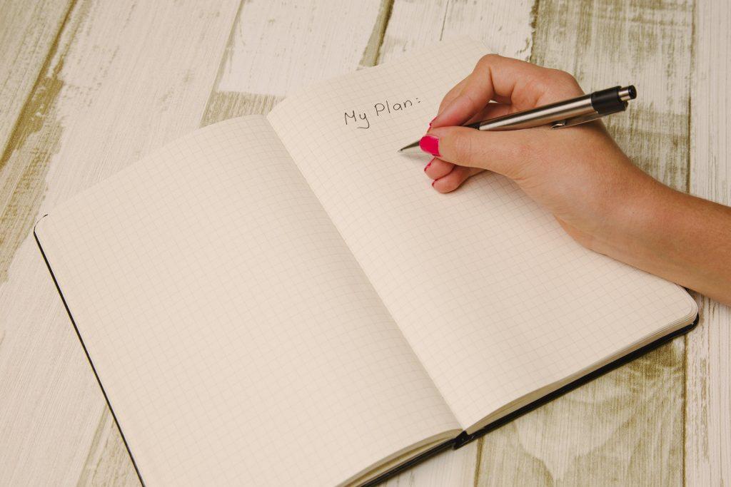 Person writing down a plan.