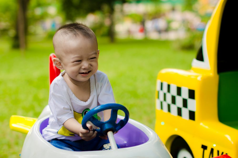 A toddler driving a car.