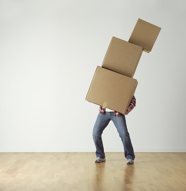 A man with moving boxes, ready to pack a moving truck.
