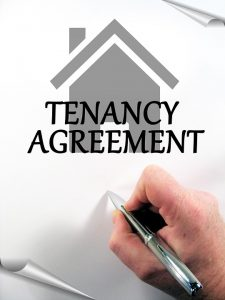 Tenancy agreement paper and a hand signing it.