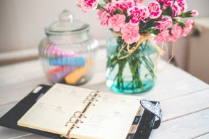 Moving - out checklist with notebook and flowers.