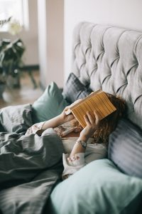 A woman laying in bed with a book on her face