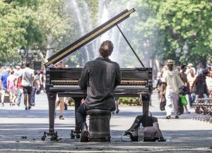 A man playing a piano in a park