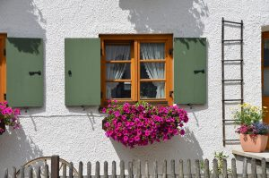 Wooden window with flowers under.