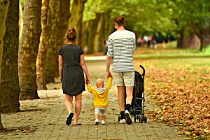 Man and woman walking with a toddler and strollers
