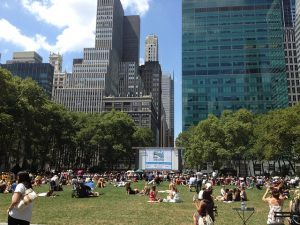 Central Park open cinema is a great place to meet your NYC neighbors , people sitting on the grass