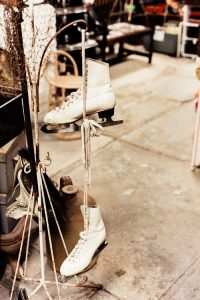 white ice skates hanging on the rack