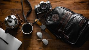 A backpack, a camera a watch and coffee on a table.