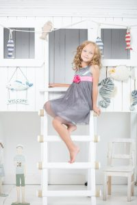 Little girl standing on the ladders.