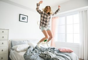 A woman jumping on a bed with joy. You can remodel your bedroom to improve your own happiness.