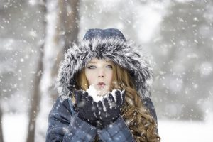 A girl in winter jacket blowing snow