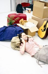 A girl is lying on the floor surrounded by packed belongings