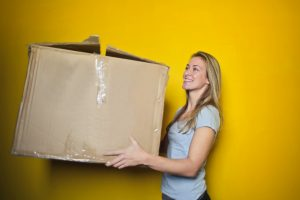 A girl holding a large cardboard box