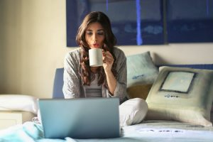 A woman drinking coffee and looking at her laptop