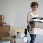 A woman carrying professional moving boxes - you should acquire the best packing and moving supplies for your move as well