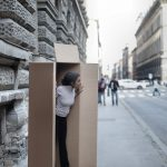 A girl peaking out of a cardboard box on the street.