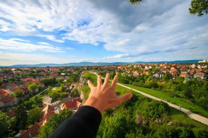 A hand raised pointing to the suburbs