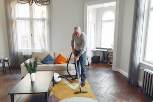 A man vacuuming the floor