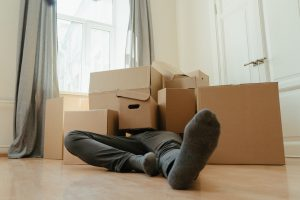 A man lying under moving boxes