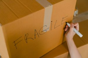 Someone marking a box as fragile