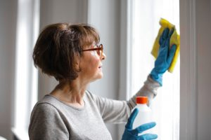A woman doing the move-in cleaning of the windows