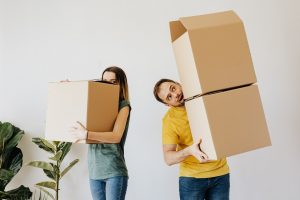A woman and a man carrying moving boxes