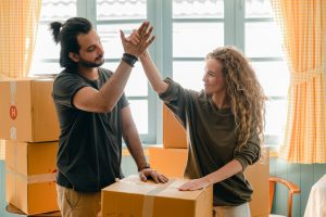 A couple giving high five surrounded by moving boxes