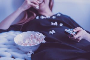 A woman watches a movie and eats popcorn