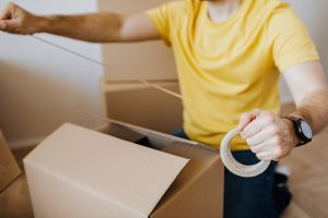 Man with cardboard boxes while packing belongings