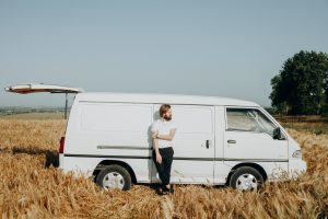 male leaning on a white van
