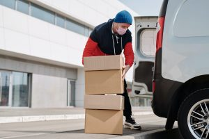male unloading a van, cardboard boxes piled up