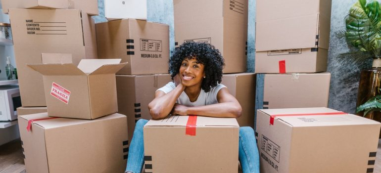 woman sitting between moving boxes