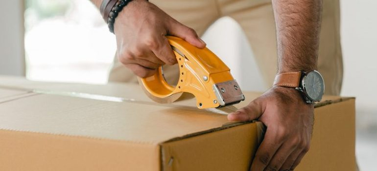 person using duct tape to close a cardboard box