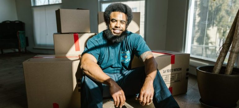 Professional mover sitting between cardboard boxes