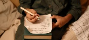 Man writing on a piece of paper.