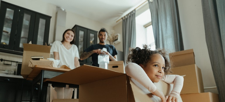 Parents look at the girl and smiling because they move to Manhattan with toddlers
