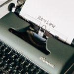 typewriter with moving review typed on the paper